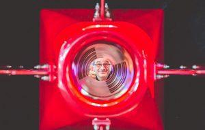 Mann blickt durch eine rote Röhre