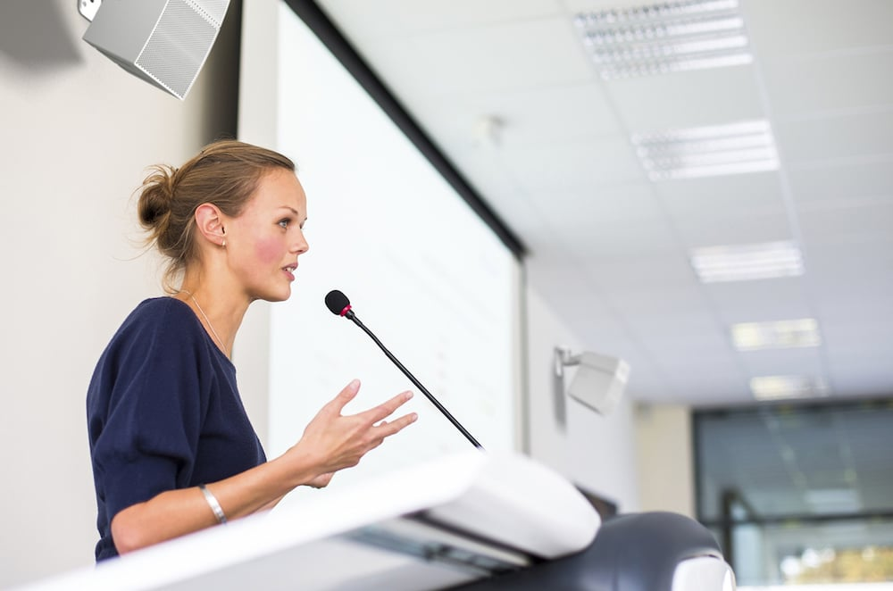 Pretty young business woman giving a presentation in a conferenc