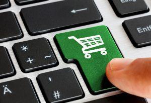 Grüner Einkaufswagen auf schwarzer Tastatur