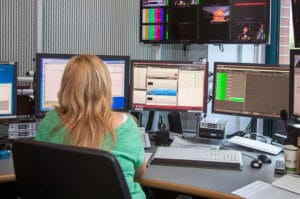Frau vor Monitoren mit VPMS von Arvato Systems