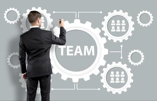 """Mann vor einer Tafel mit der Aufschrift """"Team"""""""
