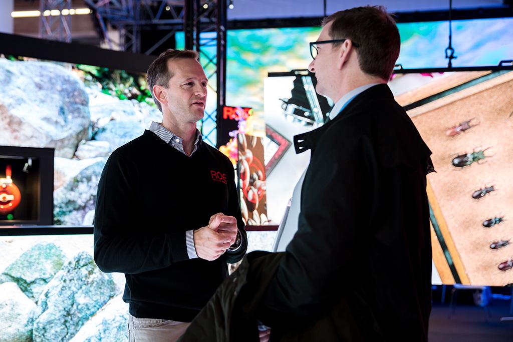 Erik Baum im Gespräch mit einem Kunden auf dem Messestand von ROE Visual