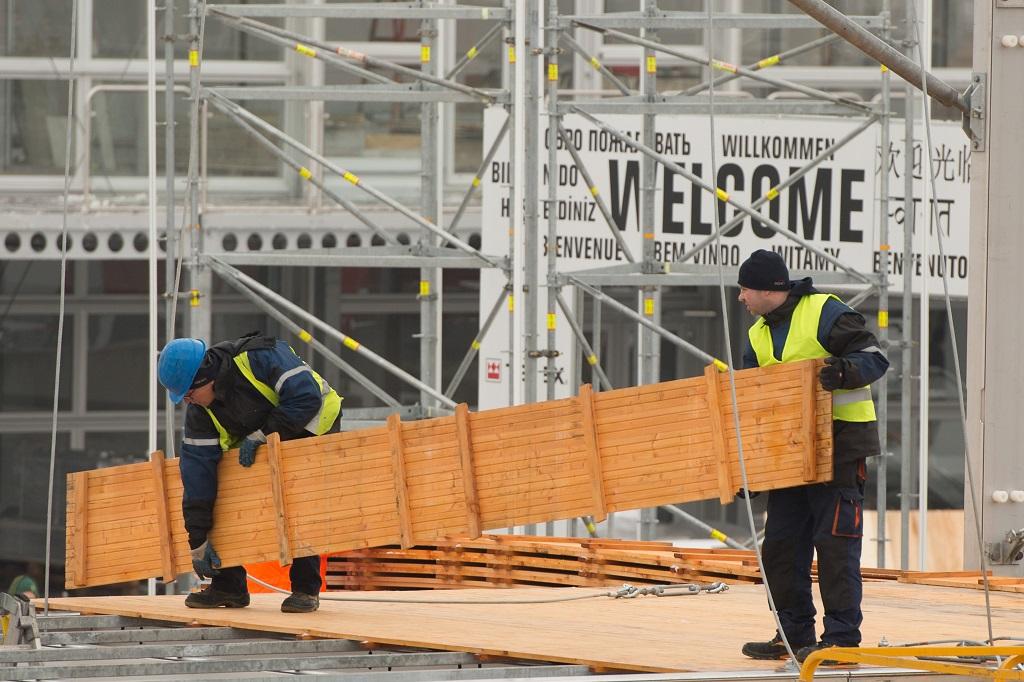 Arbeiter legen auf der Messe Muenchen waehrend dem Aufbau der bauma 2016 Holzbretter aus.
