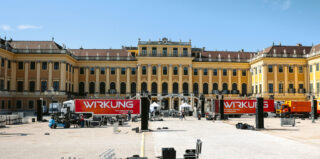 Das Schloss Schönbrunn mit zwei LKWs im Vordergrund