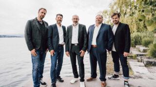 Fünf Männer stehen an einem See