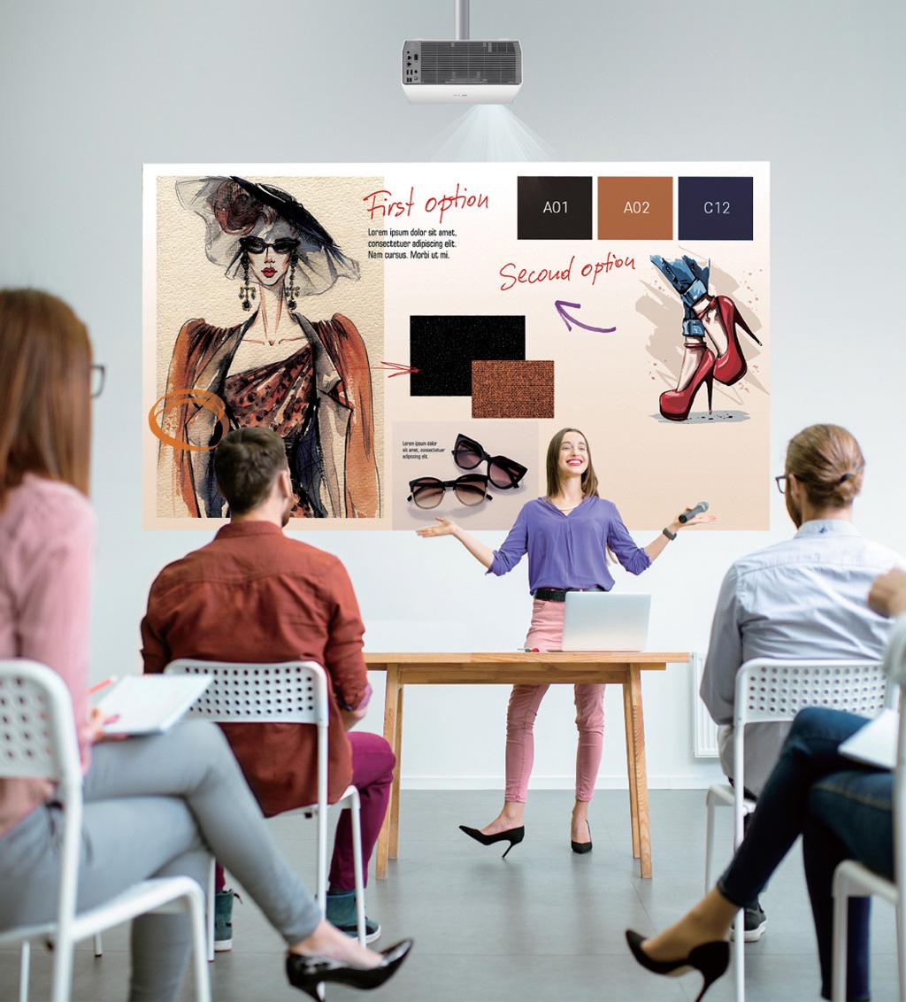 Frau steht vor einem Raum, befindet sich hinter einem Tisch und vor einer Projektion