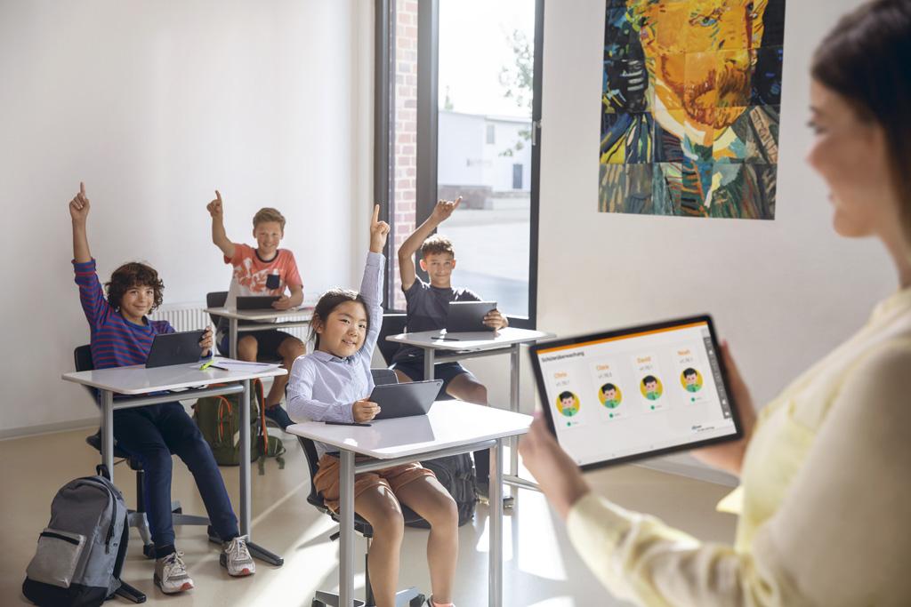 Lehrerin mit Tablet in der Hand im Klassenraum