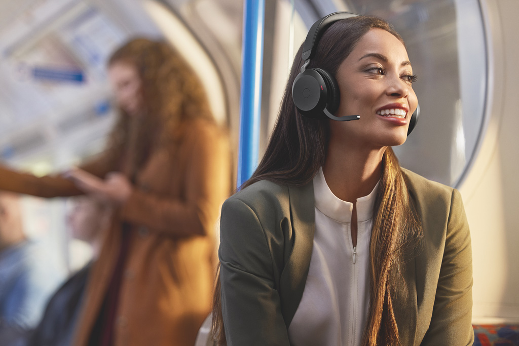 Frau sitzt in der Bahn und hört über Kopfhörer Musik