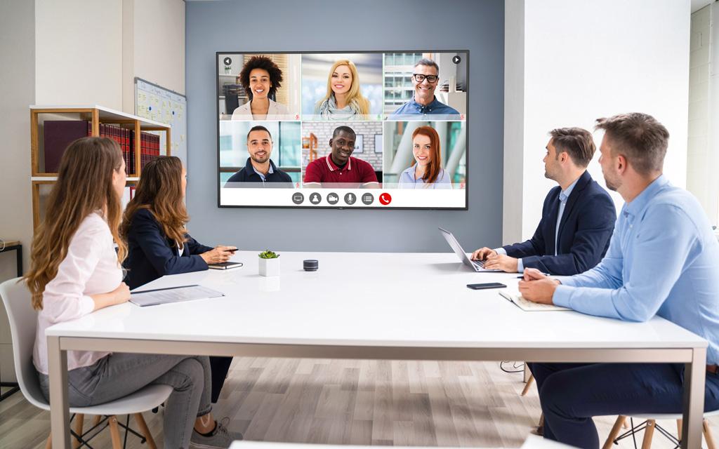 Personen in einem Konferenzraum halten eine Videokonferenz mit Leuten