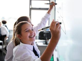 Kind schreibt mit Stift auf ein Whiteboard